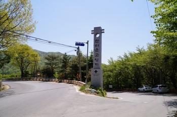 성지 입구. 왼쪽이 908번 지방도로이고, 오른쪽 내리막길이 성지로 가는 길이다.