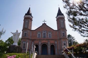 빨간 벽돌과 두 개의 첨탑을 갖고 1929년에 준공된 성당 외부.