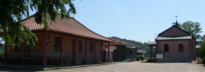 옛 성당과 사제관(현 대건의 집). 가운데 건물이 현 사제관이다.