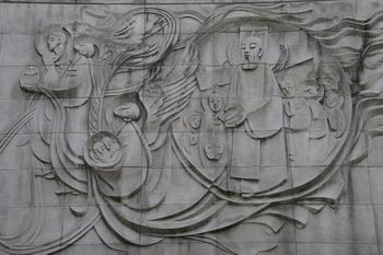 순교기념관 외벽에 부조된 이윤일 요한 성인과 많은 순교자들이 승리의 팔마가지를 들고 하느님 나라를 향하는 모습.