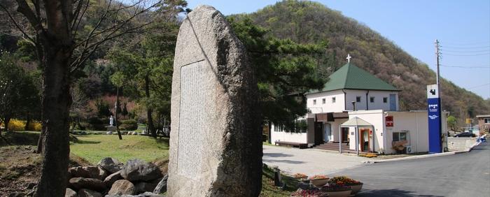 성지 입구 표지석 왼쪽으로 성 김대건 신부 동상과 야외제대, 오른쪽으로 사무실과 사제관 건물이 있다.