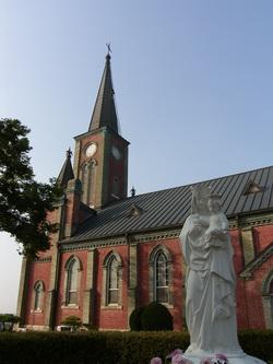 매괴 박물관 앞마당에서 본 성당 모습. 성모자상과 함께 충청북도 유형문화재 제188호로 지정된 성당 모습이 보인다.