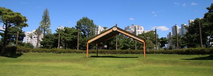 잔디광장 뒤로 십자가 기둥이 높이 솟아 있다.