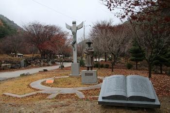 성지 입구에 건립된 한국교회 최초의 수덕자 홍유한 선생 동상과 십자가.