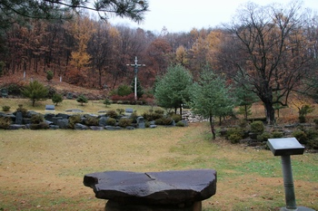 성지 전경. 야외제대 맞은편에 묘역과 대형 십자가, 성모상이 있고, 그 둘레에 십자가의 길이 조성되어 있다.