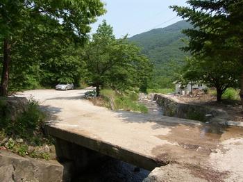 건학마을 입구. 왼쪽 공터에서 다리를 건너면 여러 채의 민가가 있다.