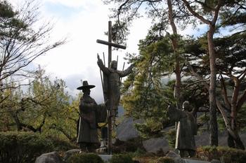 1996년 건립한 부활 예수상과 박상근 마티아 순교복자(우)와 칼래 신부의 우정상이 묘소 뒤에 자리하고 있다.