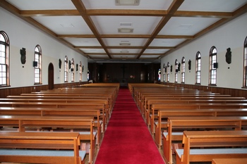 낮은 천장과 긴 평면 구조를 갖고 있는 성당 내부. 제대 옆으로는 1991년 라틴 십자형으로 증축한 공간이 있다.