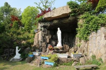 성당 옆마당의 성모동굴과 성모상. 뒷동산에는 십자가의 길이 조성되어 있다.