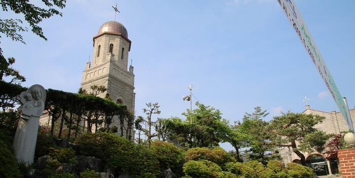 성당 입구 성모자상 뒤로 성당 종탑이 보인다.