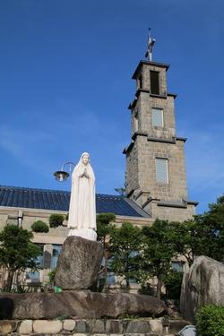 마당의 성모상과 성당 종탑.