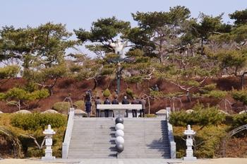 순교자 묘역 가운데 야외제대가 있고, 그 아래로 묵주기도 길 묵주알이 보인다.